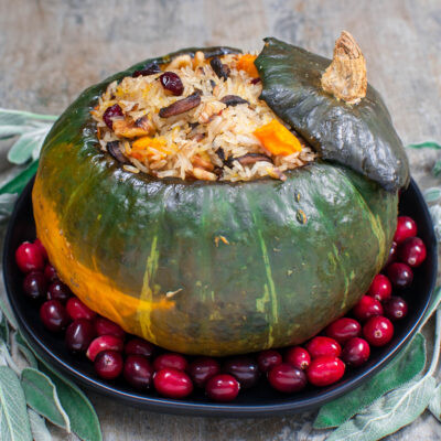 Delicious Kabocha Squash Roasted and Stuffed with Rice, Cranberries, Mushrooms, Walnuts, Onion, and Sage.