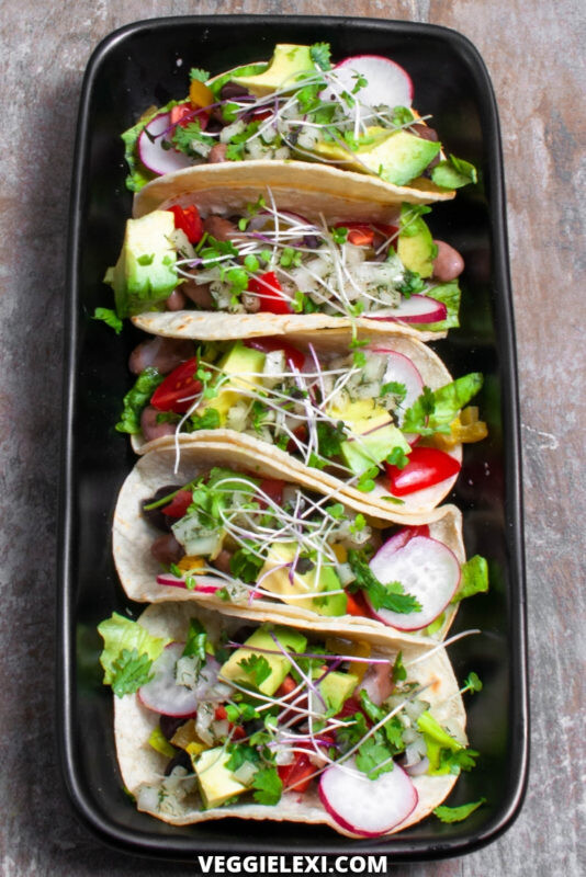 Delicious vegan, gluten free, and oil free mini taco sliders! Made with beans, fresh radish, tomato, avocado, cilantro, and sprouts. #veggielexi #veganrecipes #glutenfreerecipes #tacos